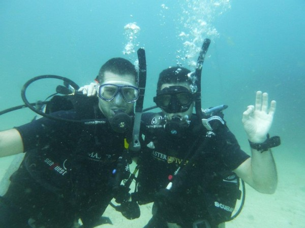 Stef and Seb scuba diving OK pose