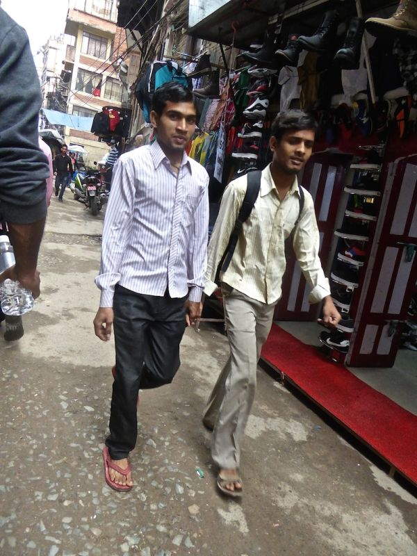 Deux amis marchent dans la rue en se tenant la main à Katmandou